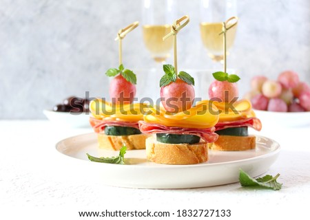 Tasty canapes with cucumber, salami, cheese and grapes served with white wine. Top view with copy space. Photo stock ©