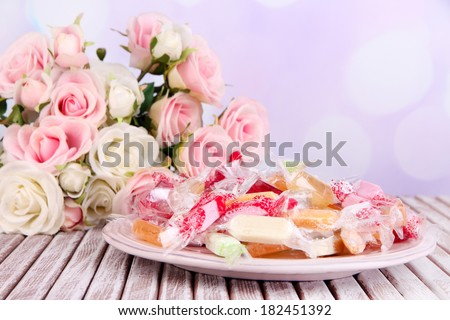 Tasty candies on plate with flowers on table on bright background