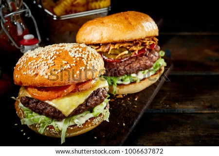 Tasty cheeseburger on a sesame bun and second beef burger on a crusty roll ready for serving on a rustic wooden board with copy space Stock photo ©