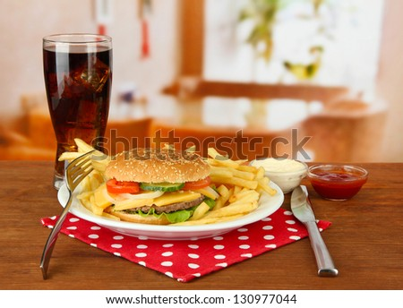 Tasty cheeseburger with fried potatoes and cold drink, on bright background