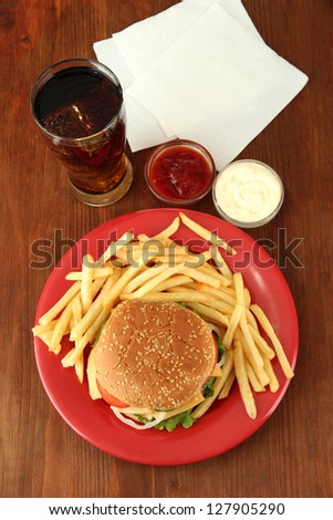 Tasty cheeseburger with fried potatoes and cold drink, on wooden background