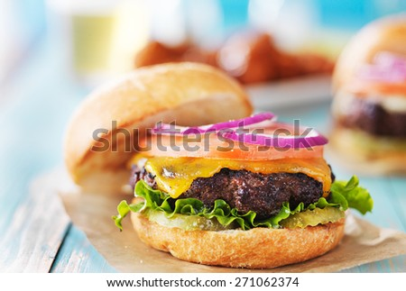 tasty cheeseburgers with wings and beer