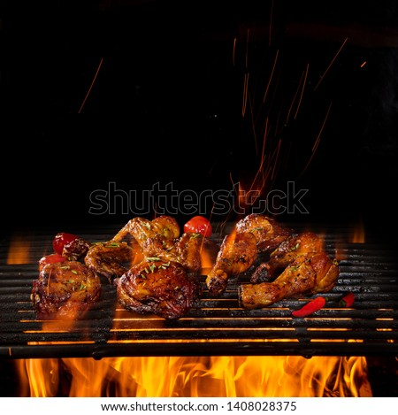 Tasty chicken legs and wings on the grill with fire flames #1408028375