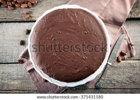 Tasty chocolate frosting cake on wooden table