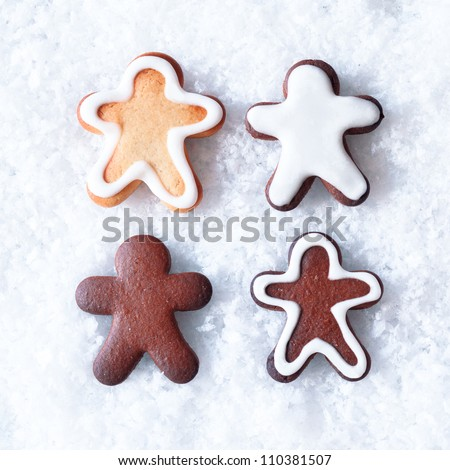 Tasty Christmas gingerbread men cookies with decorative icing lying on a bed of snow with copyspace