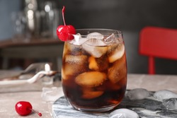 Tasty cola with ice cubes and cherry on table indoors