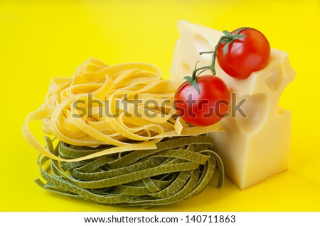 Tasty colorful bright still life of traditional Italian green and yellow pasta nests, cheese with holes, two ripe fresh shiny red cherry tomatoes with green stems on top. Yellow background, copy space