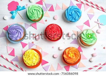 Tasty colorful cupcakes on wooden table