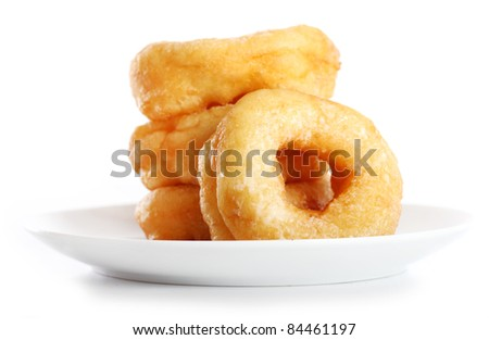 Tasty colorful donuts on the plate against white background