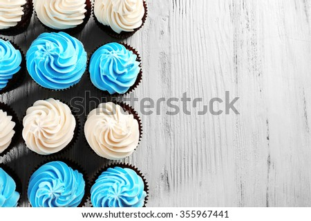 Tasty colourful cupcakes in a row on white wooden  background #355967441