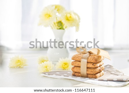 Tasty cookies on the napkin and flowers in background and on table in the morning