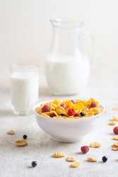 Tasty corn flakes with raspberries and blueberries on white background.Breakfast. Cornflakes with berry and milk. Cereal flakes. Fresh healthy food. Morning meal. Wooden table. Organic. Diet concept.