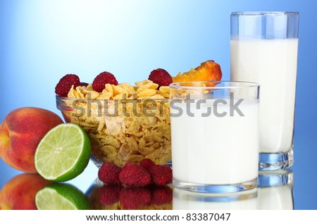 tasty cornflakes, fruit in glass bowl and milk on blue background
