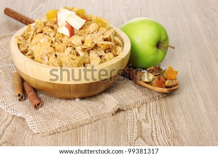 tasty cornflakes in bowl with dried fruits, glass of milk and apple on wooden table