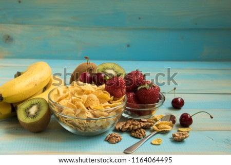 Tasty cornflakes in glass bow with walnut and strawberries, lbananas,cherry, kiwi on blue background. Corn Flakes, Copy Space #1164064495