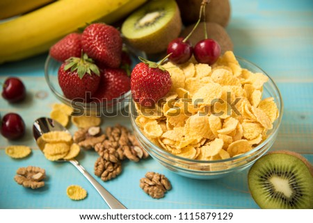Tasty cornflakes with  fruits . cornflakes on wooden table at morning #1115879129
