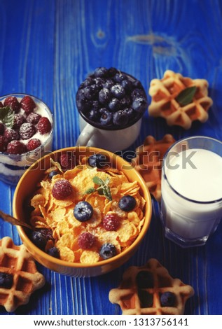 Tasty cornflakes with raspberries and blueberries on blue background. Wafers and milk. A great start to the day. Top view. #1313756141