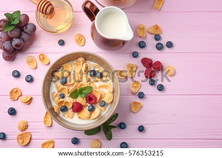 Tasty cornflakes with raspberries and blueberries on pink background #576353215