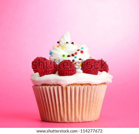 tasty cupcake with berries, on pink background