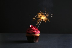 Tasty cupcake with sparkler on black background