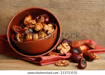Tasty dates fruits in bowls, on wooden background