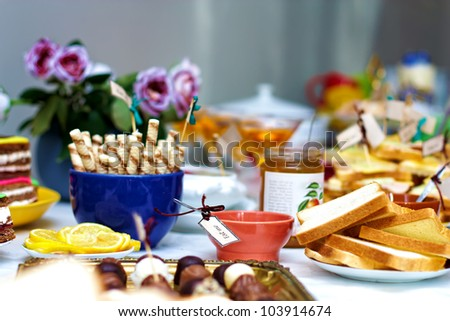 tasty delicious of English tea party, with fresh fruits, jam, biscuits and sandwiches