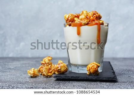Tasty dessert. Glass of homemade yogurt with caramel popcorn and sweet sauce on black slate board on gray concrete background