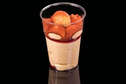 Tasty dessert tiramisu cake in a cup, isolated on black background, with reflection