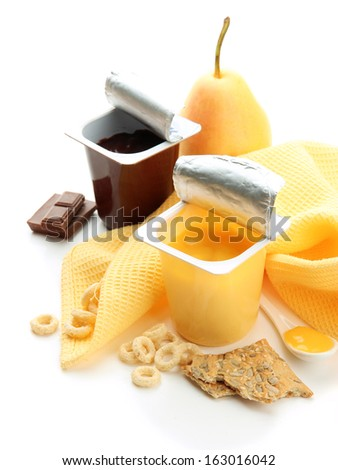 Tasty desserts in open plastic cups and fruits and flakes on napkin, isolated on white