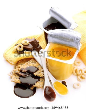 Tasty desserts in open plastic cups and honey combs, fruits and flakes on napkin, isolated on white