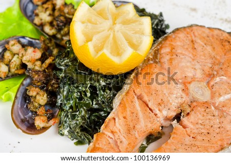 Tasty dish of salmon steak with algae mussels, lemon and kiwi - stock photo