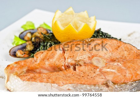 Tasty dish of salmon steak with algae mussels, lemon and kiwi