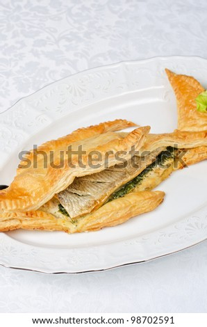 tasty dish of trout fish baked with greens at dough