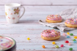 Tasty donuts with pink icing, colorful sprinkles and jelly beans on wooden background. Sweet pastry as a snack for children's birthday party or other celebrations. Pastel colors, light and airy.