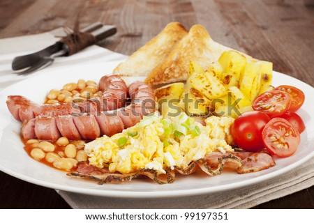 Tasty english breakfast. Sausages, scrambled eggs, potatoes, beans ...