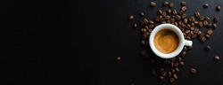 Tasty espresso served in cup with coffee beans around and spoon. View from above. Dark background. Banner.