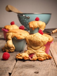 Tasty failed raspberry muffins with organic ingredients on a wooden kitchen table