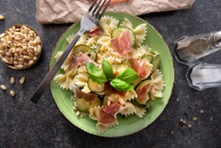Tasty farfalle pasta with courgette, prosciutto ham, grana padano cheese and pine nuts