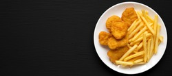 Tasty Fastfood: Chicken Nuggets and French Fries on a plate on a black surface, top view. Flat lay, overhead, from above.