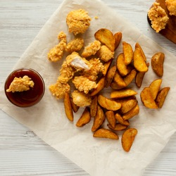 Tasty fastfood: fried potato wedges, chicken bites with barbecue sauce on a white wooden surface, top view. Flat lay, overhead, from above.