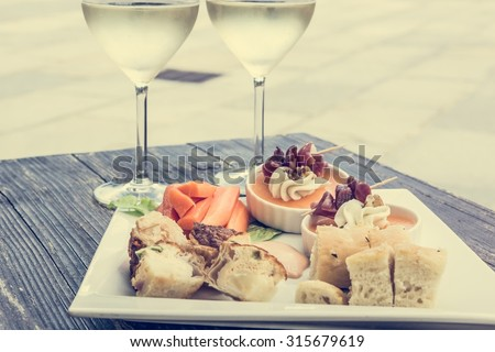 Tasty finger food on a wooden table. With a pair of wine glasses.