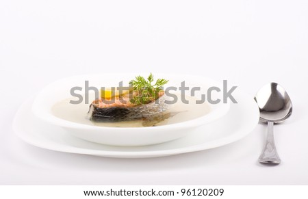 Tasty fish soup with salmon and lemon on a white background