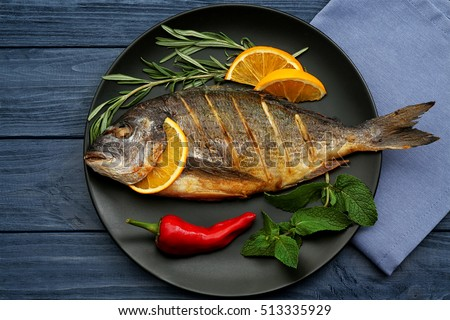 Tasty fish with vegetables and lemon on kitchen table