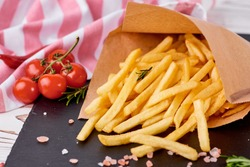 Tasty french fries on a black board