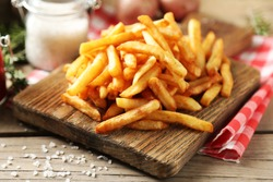 Tasty french fries on cutting board, on wooden table background