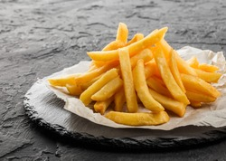 Tasty french fries potatoes on paper over black stone background. Hot fast food, close up