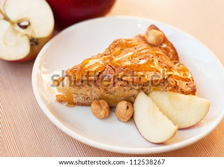 Tasty fresh apple pie with slices of apple and hazelnuts covered with honey on a white plate on a kitchen table