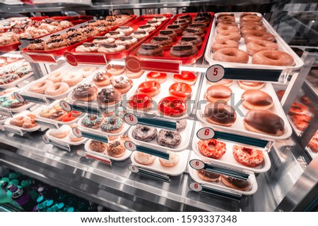 Tasty fresh donuts at confectionery shop counters for sale