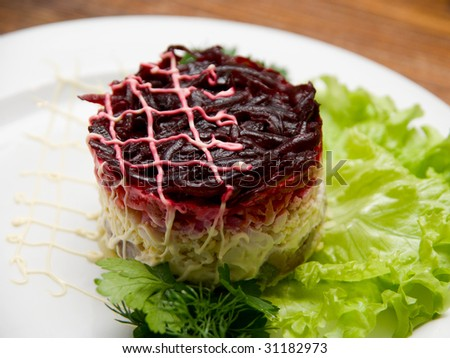 Tasty fresh healthy salad with herring on wooden table background. Russian dish.