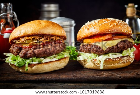 Tasty fresh meat burgers with salad and cheese served on wooden board